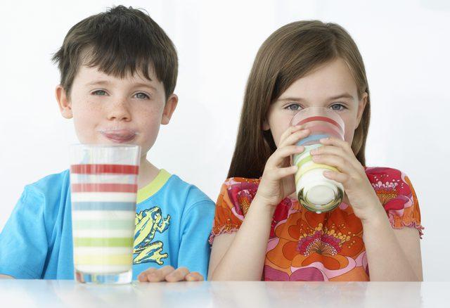 девочка и мальчик пьют молоко из стаканов